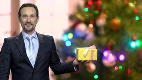 Homme d'affaires bel tenant le cadeau de Noël banque de vidéos
