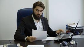 Homme d'affaires bel travaillant avec l'ordinateur portable dans le bureau Jeune homme d'affaires avec un fonctionnement de barbe images libres de droits