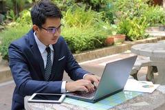 Homme d'affaires bel travaillant avec l'ordinateur portable dehors en parc Photo libre de droits