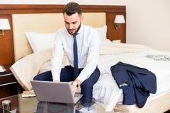 Homme d'affaires bel Using Laptop dans la chambre d'hôtel Image libre de droits