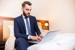 Homme d'affaires bel utilisant l'ordinateur dans la chambre d'hôtel Image stock