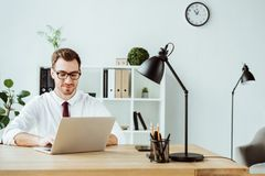 homme d'affaires bel utilisant l'ordinateur portable à l'espace de travail Photo stock
