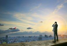 Homme d'affaires binoculaire à l'homme avec la fusée sur le vol arrière au-dessus de ci Images stock