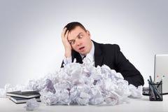 Homme d'affaires bouleversé avec le papier chiffonné dans le bureau sur le fond gris Image stock