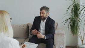 Homme d'affaires bouleversé ayant la consultation avec le psychologue féminin clips vidéos
