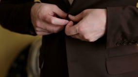 Homme d'affaires boutonnant un bouton sur sa veste brune banque de vidéos