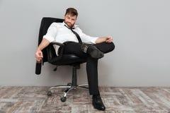 Homme d'affaires bu heureux s'asseyant dans la chaise de bureau avec la bouteille Image libre de droits