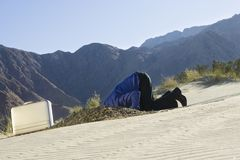 Homme d'affaires Burying Head In le sable Image stock
