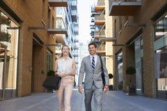 Homme d'affaires And Businesswoman Walk à travailler par la rue de ville photos stock