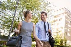 Homme d'affaires And Businesswoman Walk à travailler par le parc de ville image libre de droits
