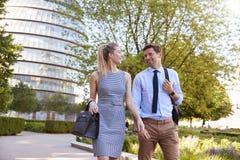 Homme d'affaires And Businesswoman Walk à travailler par le parc de ville images libres de droits