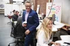 Homme d'affaires And Businesswoman Working à l'ordinateur portable sur le bureau dans le bureau ouvert de plan photographie stock libre de droits