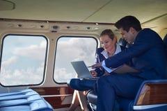 Homme d'affaires And Businesswoman Working sur l'ordinateur portable dans l'hélicoptère Ca photos stock