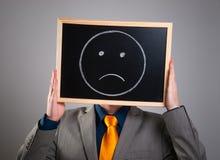 Homme d'affaires cachant son visage avec un panneau d'affichage blanc avec un fa triste Photos stock