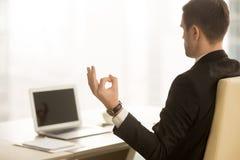 Homme d'affaires calme méditant dans le lieu de travail, mudra de menton, yoga à l'OE Photos libres de droits