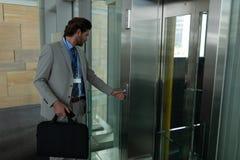 Homme d'affaires caucasien attendant l'ascenseur dans le bureau moderne photo stock