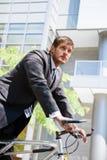 Homme d'affaires caucasien conduisant un vélo Images stock