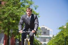 Homme d'affaires caucasien conduisant une bicyclette image libre de droits