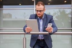 Homme d'affaires caucasien en dehors de bureau utilisant le téléphone portable et le tabl images stock