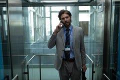 Homme d'affaires caucasien parlant au téléphone portable dans l'ascenseur moderne au bureau photo stock