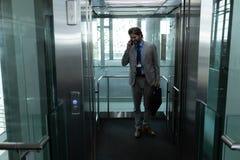 Homme d'affaires caucasien parlant au téléphone portable dans l'ascenseur moderne au bureau image stock