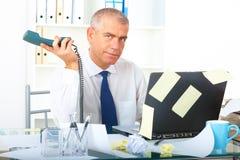 Homme d'affaires chargé s'asseyant au bureau photographie stock