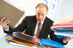Homme d'affaires chargé avec le travail Photos stock
