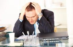 Homme d'affaires chargé s'asseyant au bureau Photographie stock libre de droits