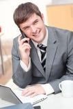 Homme d'affaires charismatique utilisant l'ordinateur portatif tout en téléphonant image stock