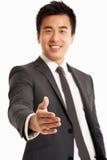 Homme d'affaires chinois atteignant à l'extérieur pour secouer Han Photos libres de droits