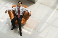 Homme d'affaires chinois détendant dans un fauteuil images stock