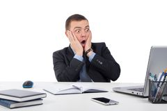 Homme d'affaires choqué avec l'ordinateur portable et documents au bureau Photos stock