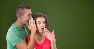 Homme d'affaires chuchotant dans l'oreille choquée du ` s de collègue sur le fond vert photographie stock