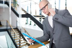 Homme d'affaires With Clipboard Using Smartphone dans le bureau image stock