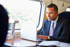 Homme d'affaires Commuting To Work sur le train et l'ordinateur portable d'utilisation Photo stock