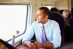 Homme d'affaires Commuting To Work sur le train utilisant le téléphone portable Photographie stock libre de droits