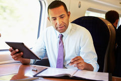 Homme d'affaires Commuting On Train à l'aide de la Tablette de Digital Photos libres de droits