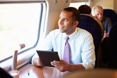 Homme d'affaires Commuting On Train à l'aide de la Tablette de Digital Photo libre de droits