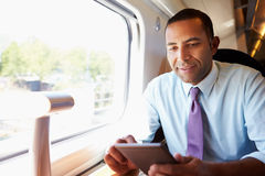 Homme d'affaires Commuting On Train lisant un livre Photos stock