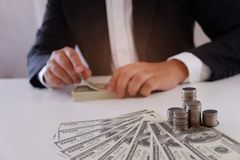 Homme d'affaires comptant l'argent avec des pièces de monnaie et l'argent au-dessus du bureau images stock
