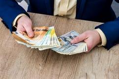 Homme d'affaires comptant le dollar et l'euro image libre de droits