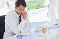 Homme d'affaires concentré analysant des graphiques photographie stock
