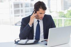Homme d'affaires concentré ayant un appel téléphonique et travaillant au sien Photos stock