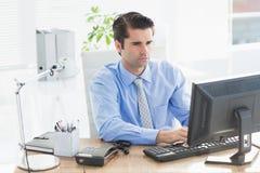 Homme d'affaires concentré dactylographiant sur le clavier images libres de droits