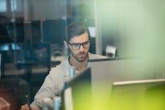Homme d'affaires concentré travaillant sur l'ordinateur au bureau images stock