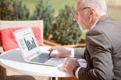 Homme d'affaires concentré travaillant sur l'ordinateur portable Photo stock