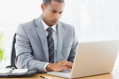 Homme d'affaires concentré utilisant l'ordinateur portable au bureau photo stock