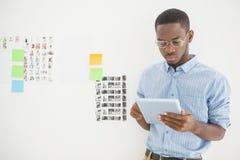 Homme d'affaires concentré utilisant le PC de comprimé photographie stock
