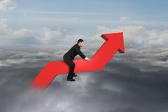 Homme d'affaires conduisant la ligne de tendance 3D rouge dans le ciel Photo stock