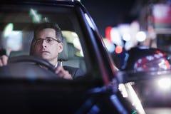 Homme d'affaires conduisant la nuit dans la ville Photographie stock